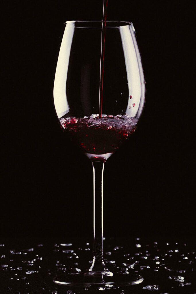 Et glas vin, hvori der hældes mere vin i.